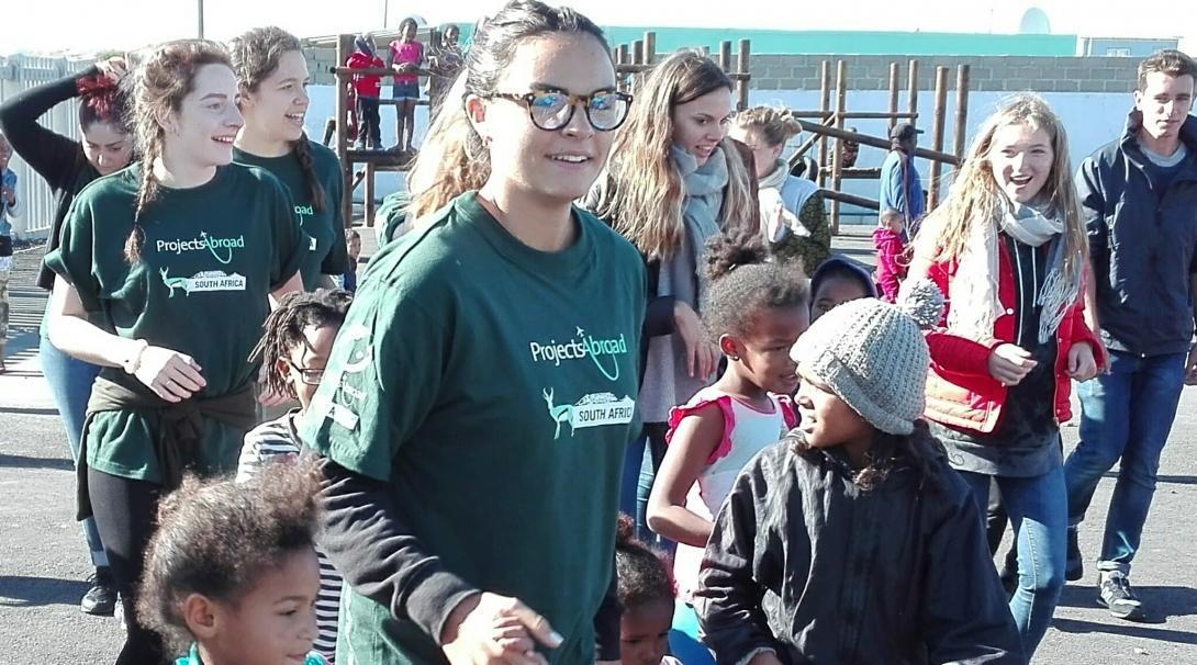Voluntaria toma de la mano a niños durante caminata en su voluntariado social.